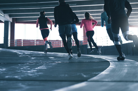 Back view of athletes in sportswear running on race track in gym.