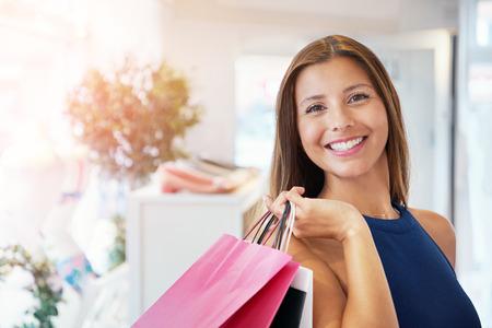 화려한 성인 구매자 저장소에 그녀의 어깨 너머로 모듬 된 종이 쇼핑백을 들고. 복사본 공간이 포함되어 있습니다.