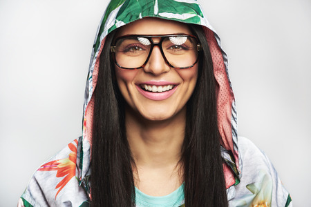 Attractive friendly young Indian woman in glasses wearing a hooded top looking at the camera with a wide beaming smile isolated on white