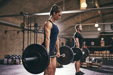 Strong woman and man holding heavy barbells in gym. Horizontal indoors shot Foto de archivo