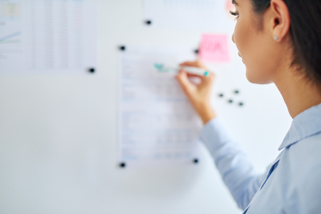 Selective focus over the shoulder view of woman writing on sheets of paper tacked to bulletin board