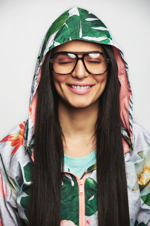 Beautiful woman in fashion glasses and colorful sports jacket with green hood, smiling with eyes closed, close-up front portrait against white background
