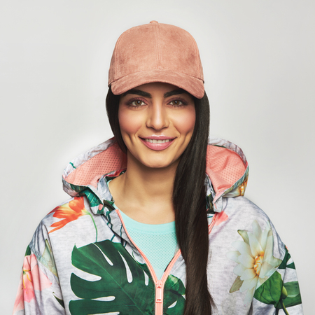Pretty young woman in a peaked cap and floral hoodie with her long hair over one shoulder looking at the camera with a warm friendly smile