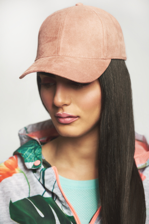 Beautiful woman with make-up and long black hair in pink cap and sports outfit looking away, close-up portrait Stock Photo