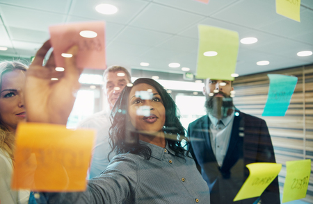 Businesswoman putting sticky note on glass, group of colleagues behind her Zdjęcie Seryjne