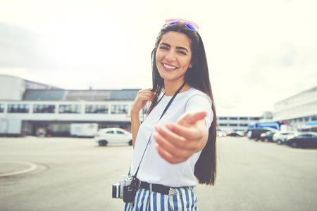 Cute young woman holding out her hand in a gesture of invitation as she stands smiling at the camera in town