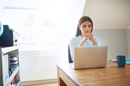 Thoughtful concerned young businesswoman sitting working at a wooden table in a home office staring ahead with a pensive expression Stock Photo