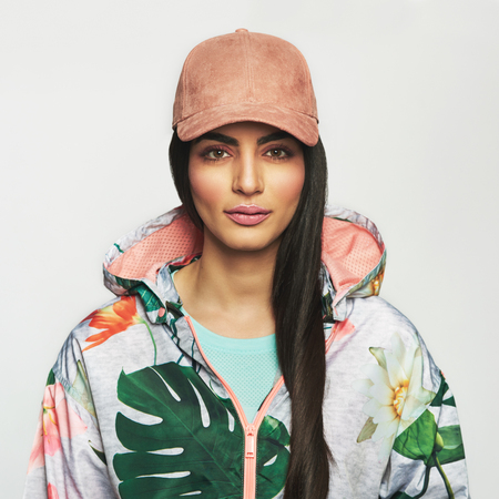 inscrutable: Beautiful young woman with make-up and long black hair wearing colorful sports jacket and yellow cap, looking ahead at camera, close-up front portrait against white background