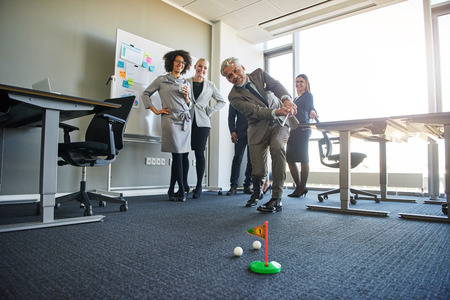 Business people teambuilding in office space with mini golf, laughing looking positive Stock Photo