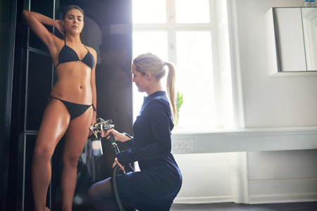 Beautician using aerograph for spray tan apply to young pretty female leg in beauty salon. Stock Photo