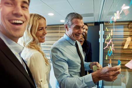 付箋にはガラスの仕切りの横にあるビジネス チームを笑っている場合 office、フォア グラウンドでカメラに向かっている男