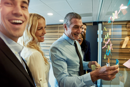Smiling business team next to sticky notes on glass partition if office, man looking towards camera in foreground Imagens
