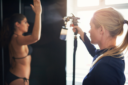 Cosmetologist using airbrush for spray tan apply to young woman hand in beauty salon.