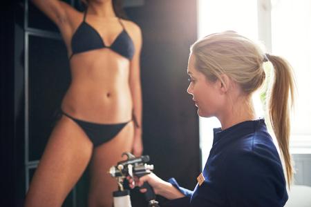 spray: El cosmetólogo que usa el aerograph para el tan del aerosol aplica a la pierna de la mujer joven en salón de belleza.