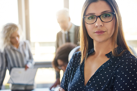 Serious business woman in front of team in office, looking at camera Stock Photo