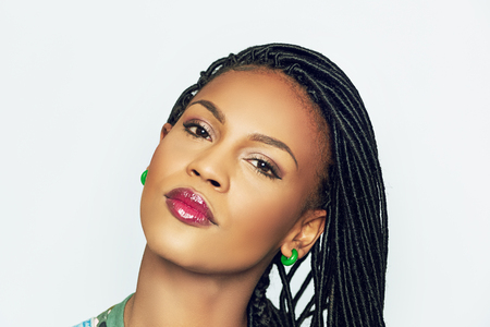 Head shot of African girl with braids and vibrant green earrings looking at camera emotionless isolated on white