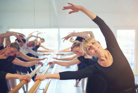 Cheerful adult female ballet dancer looking at camera and stretching with hand up.