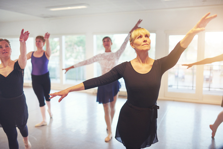 Group of adult ballerinas standing with hands up in class for ballet performing a dance. Imagens
