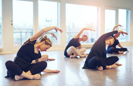 Women dancing ballet while sitting and stretching with hands up on the floor of class. 스톡 콘텐츠