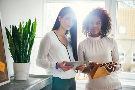 Zwei junge moderne gemischtrassige Designer, die die Tablette surfen und an einem Projekt am Arbeitsplatz nahe Fensterbrett arbeiten. Standard-Bild - 79636706