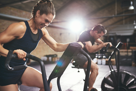 Sportive man and woman using equipment in spacious light gym and exercising hardly.