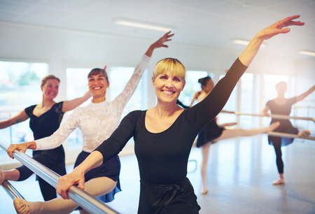 Cheerful adult women dancing ballet standing with hands up and looking at camera in the class.