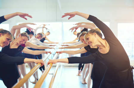 Cheerful mature ballerinas stretching with hands up standing at mirror in ballet class. Stockfoto