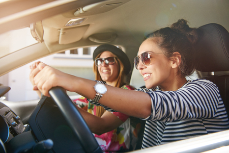 Two gorgeous young woman driving through town in a car chatting and smiling, close up through the open window with focus to the driver Stock Photo