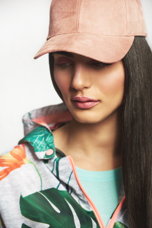 Vogue woman in urban stylish jacket and cap posing in studio and looking away. Stock Photo