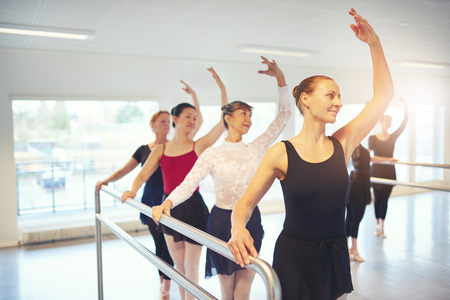 Smiling mature group of ballet performers standing and dancing with hands up in the class. Stock Photo