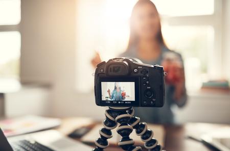 청량 음료를 들고 vlog를 만드는 젊은 여자. 스톡 콘텐츠