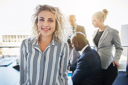 Business woman standing in front of team smiling, Team of mixed entrepreneurs