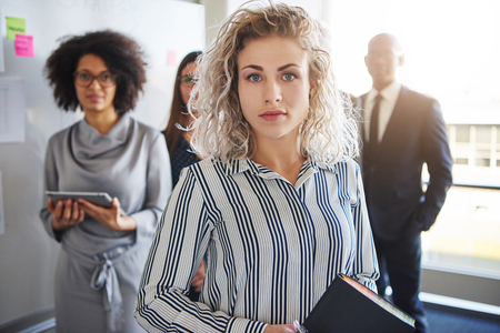 Business woman standing in front of colleagues, mixed races people looking positive Stock Photo