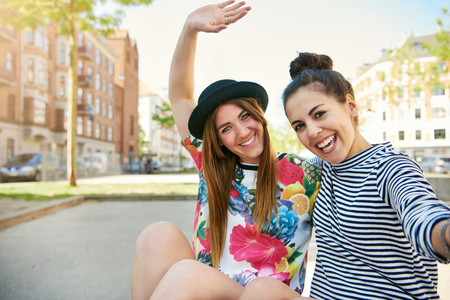 cul de sac: Vivacious friendly young women waving and laughing at the camera as they sit arm in arm in a quiet urban cul de sac Stock Photo