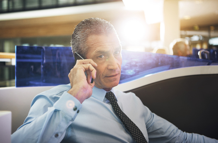 to contemplate: Mature businessman sitting in office and having phone conversation looking at camera.