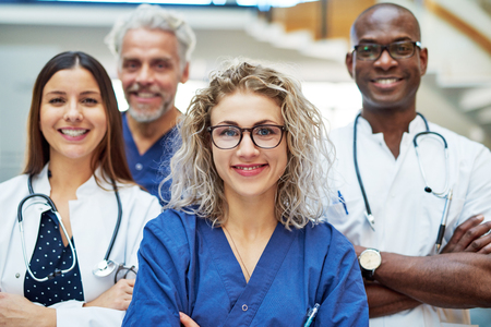 Cheerful people working in the medicine looking at camera standing with arms crossed in the hospital. Team of positive doctors