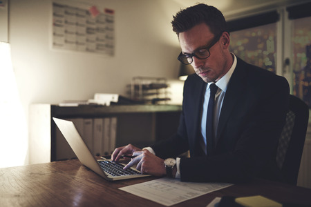 Serious businessman working on laptop at night sitting in office looking concentrated