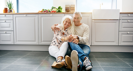 Happy mature attractive woman and handsome man embracing while sitting on kitchen floor. Large cabinets surround them.