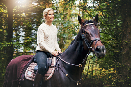 Portrait of a smiling woman riding the horse against background of green leaves