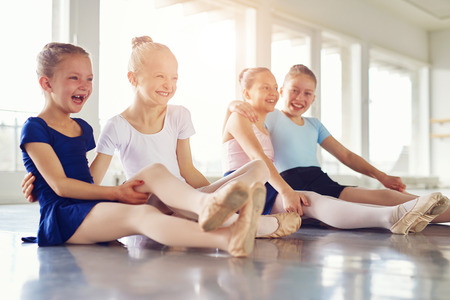 Cheerful young ballerinas smiling and embracing sitting on floor in ballet class together. Stock Photo