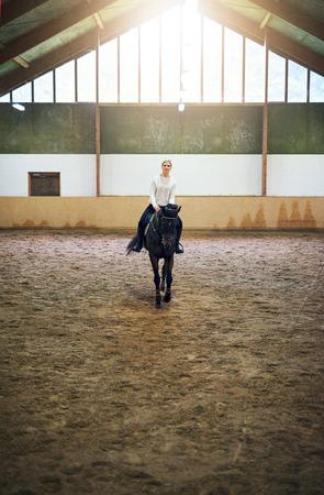 실내 승마 홀에서 어두운 말을 뛸 금발 여성 훈련