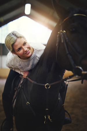 Smiling blonde female sitting astride black horse leaning on its back.