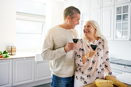 Laughing affectionate retired couple drinking a glass of wine together in the kitchen smiling happily as they look into each others eyes, with copy space Stock Photo