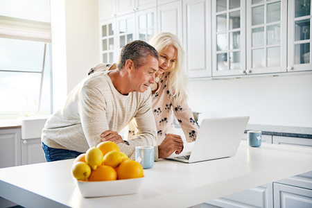 Healthy happy retired couple browsing the internet together on a laptop computer in a bright white kitchen with a bowl of fresh oranges and lemons in the foreground