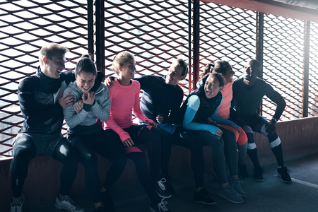 Photo of young athletics adults in sportswear sitting together and laughing against barred window. Stock Photo
