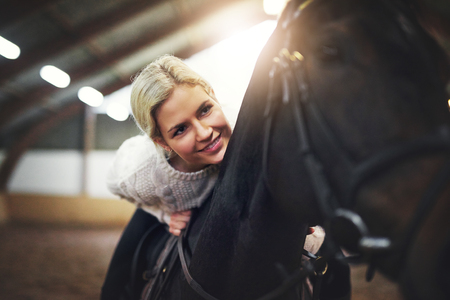 Blonde smiling female riding black horse and leaning on its back.