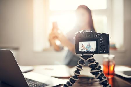 カメラのビデオ podcast をしている間、selfie を取る若い女性ブロガーを記録します。 写真素材