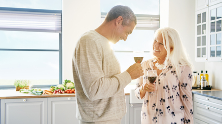 Happy retired couple raising a toast smiling into each others eyes as they enjoy a glass of red wine in a high key white kitchen