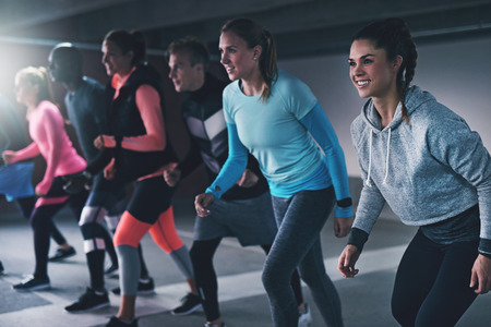 Group of young athletes working out in an urban indoor car park lining up ready to run a race or practice their sprinting with happy smile in a health and fitness concept Reklamní fotografie