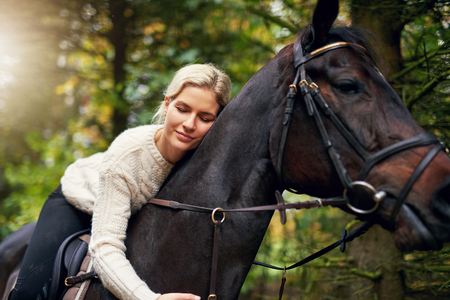 Portrait of a blond woman hugging a brown horse while in saddle